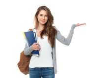 Retrato del estudiante feliz que muestra algo aislado en los vagos blancos Imagen de archivo libre de regalías