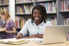 Retrato del estudiante femenino Working At Laptop de la High School secundaria en Libr fotos de archivo libres de regalías