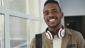 Retrato del estudiante hermoso joven de la pertenencia étnica afroamericana que se coloca en el pasillo espacioso blanco ancho de almacen de video