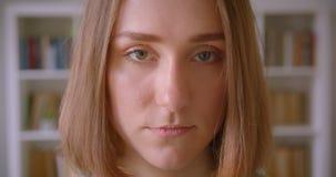 Retrato del estudiante joven caucásico que mira seriamente en cámara en casa almacen de video
