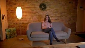 Retrato del estudiante joven que se sienta en el sofá y que mira atento la película en atmósfera casera acogedora metrajes