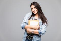 Retrato del estudiante joven que sostiene un libro sobre fondo gris Imagen de archivo
