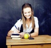 Retrato del estudiante lindo feliz con el libro en sala de clase Imagen de archivo libre de regalías