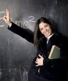 Retrato del estudiante lindo feliz en la pizarra Foto de archivo