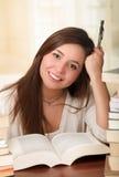 Retrato del estudiante listo con el libro abierto que lo lee en la biblioteconomía de universidad una pluma Imagen de archivo libre de regalías