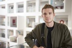 Retrato del estudiante masculino adulto joven en el entresuelo en universidad Imagen de archivo libre de regalías