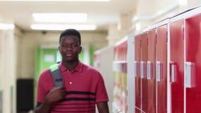 Retrato del estudiante masculino Walking Down Corridor y sonrisa de la High School secundaria en la cámara almacen de video