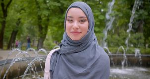Retrato del estudiante musulm?n bonito en hijab que sonr?e modesto en la c?mara que se coloca cerca de la fuente almacen de video