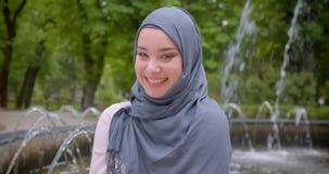 Retrato del estudiante musulmán bonito en hijab que sonríe situación principal feliz y de la inclinación cerca de la fuente almacen de video
