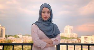 Retrato del estudiante musulmán en hijab que mira en la situación de la cámara en el balcón con la gran opinión de la ciudad almacen de metraje de vídeo