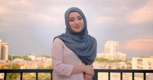 Retrato del estudiante musulmán en hijab que sonríe en la situación de la cámara en el balcón con la gran opinión de la ciudad metrajes