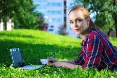 Retrato del estudiante o de la colegiala adolescente en parque con el ordenador portátil Fotografía de archivo libre de regalías