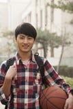 Retrato del estudiante, sonriendo y llevando a cabo baloncesto en campus de la universidad Fotografía de archivo libre de regalías