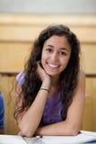 Retrato del estudiante sonriente que se inclina en su mano foto de archivo libre de regalías