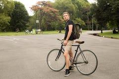 Retrato del estudiante universitario joven moderno con la bici en el parque Imagen de archivo libre de regalías