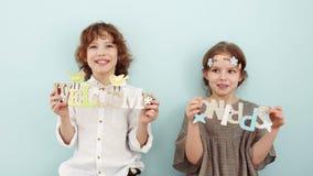 Retrato del estudio de alumnos lindos con las muestras de madera Días de fiesta de la primavera, colores en colores pastel El muc almacen de video