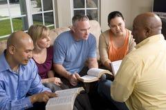 Retrato del estudio de la biblia de los amigos en casa Imagenes de archivo