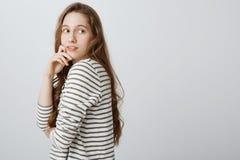 Retrato del estudio de la muchacha caucásica blanda encantadora que se coloca en perfil y que da vuelta a la derecha, sosteniendo Imagen de archivo libre de regalías