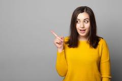Retrato del estudio de la muchacha sorprendida que señala el finger lejos Fotos de archivo libres de regalías
