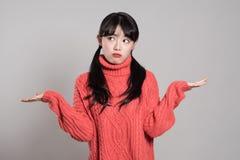 Retrato del estudio de la mujer asiática femenina de 20 años con ambas manos en la situación absurda Foto de archivo