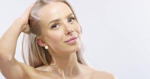 Retrato del estudio de una mujer joven sonriente con el pelo rubio largo almacen de metraje de vídeo