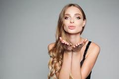 Retrato del estudio de una mujer rubia atractiva con el pelo grueso largo y el maquillaje profesional que llevan una plata elegan fotos de archivo