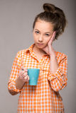 Retrato del estudio de una mujer soñolienta en una camisa anaranjada con una taza Imagen de archivo