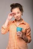 Retrato del estudio de una mujer soñolienta en una camisa anaranjada con una taza Fotos de archivo libres de regalías