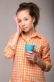 Retrato del estudio de una mujer soñolienta en una camisa anaranjada con una taza Foto de archivo
