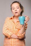 Retrato del estudio de una mujer soñolienta en una camisa anaranjada con una taza Imagenes de archivo