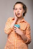 Retrato del estudio de una mujer soñolienta en una camisa anaranjada con una taza Fotografía de archivo