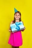 Retrato del estudio de una niña que lleva un sombrero del partido en su cumpleaños Foto de archivo