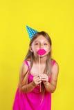Retrato del estudio de una niña que lleva un sombrero del partido en su cumpleaños Fotografía de archivo