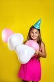 Retrato del estudio de una niña que lleva un sombrero del partido en su cumpleaños Muchacha feliz con los globos coloridos Imágenes de archivo libres de regalías