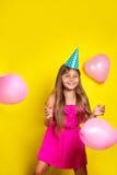 Retrato del estudio de una niña que lleva un sombrero del partido en su cumpleaños Muchacha feliz con los globos coloridos Foto de archivo libre de regalías
