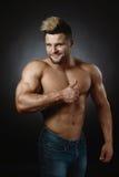 Retrato del estudio del deportista muscular con las tetas al aire con los pulgares para arriba Fotos de archivo
