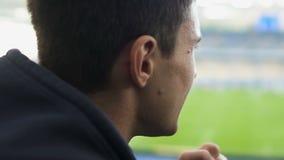 Retrato del fanático del fútbol con el partido de observación de la espinilla en el estadio, equipo de apoyo metrajes