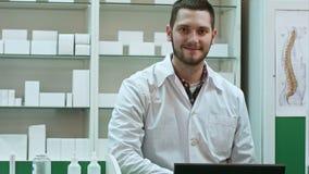 Retrato del farmacéutico de sexo masculino joven que mira la cámara y la sonrisa almacen de metraje de vídeo