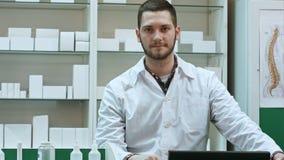 Retrato del farmacéutico de sexo masculino joven que mira la cámara y la sonrisa imagenes de archivo