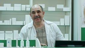 Retrato del farmacéutico mayor que sonríe y que habla con una cámara almacen de metraje de vídeo