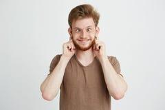 Retrato del feliz hombre joven alegre que hace la cara divertida que engaña sobre el fondo blanco Fotografía de archivo
