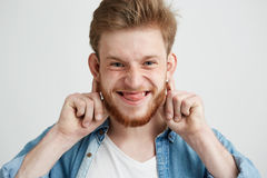Retrato del feliz individuo alegre joven que hace la cara divertida que engaña mirando la cámara que muestra la lengua sobre el f Imagenes de archivo
