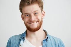 Retrato del feliz individuo alegre joven que hace la cara divertida que engaña mirando la cámara sobre el fondo blanco Foto de archivo