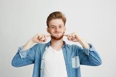 Retrato del feliz individuo joven alegre que hace la cara divertida que engaña mirando la cámara sobre el fondo blanco Foto de archivo libre de regalías