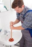 Retrato del fontanero de sexo masculino que presiona el émbolo Imagen de archivo