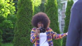 Retrato del fotógrafo afroamericano joven sonriente positivo de la mujer en la calle en parque almacen de metraje de vídeo