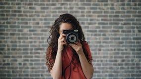 Retrato del fotógrafo de la señora joven que toma la foto con la sonrisa de la cámara almacen de metraje de vídeo