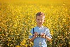 Retrato del fotógrafo del niño pequeño con la cámara en fondo del campo del amarillo de la puesta del sol foto de archivo libre de regalías