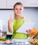Retrato del freelancer de sexo femenino con los documentos en la tabla de cocina Foto de archivo