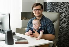 Retrato del freelancer de sexo masculino joven sonriente que se sienta en Ministerio del Interior y que detiene a su hijo de 1 añ imagen de archivo libre de regalías